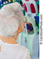old woman with white hair sitting back to camera
