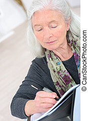 old woman writing notes at home