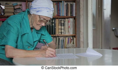 old woman writing take off glasses