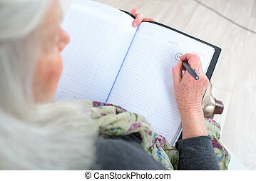old woman writing the diary
