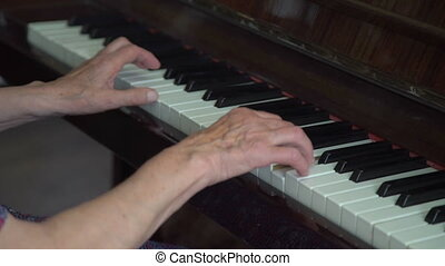 Old woman's hands playing the piano