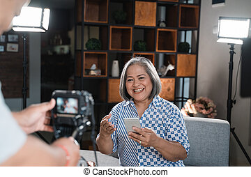 Old women making a video on mobile phone technology