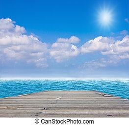 old wood bridge to blue sea
