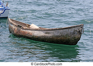Old Wood Canoe - An old wooden canoe afloat in the bay