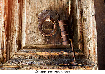 Old wood door etched in Arabic with Roman letters carved below, with an original metal door knocker. The key holder is attached to the door knocker, on the door of the Church of the Holy Sepulcher.