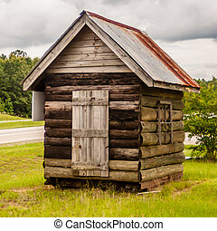 Old solid log cabin shelter near road and the forest