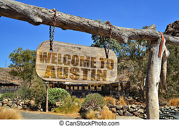 "wood signboard with text "" welcome to Austin"" hanging on a branch"