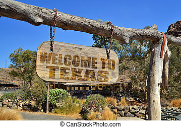 "old wood signboard with text "" welcome to texas"" hanging on a branch"