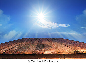 old wood table and sun shine on blue sky