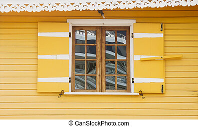 Old Wood Window in Bright Yellow Wall