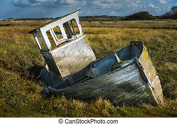 Old rotting fishing boat on dry land