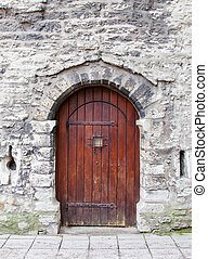 Old wooden arched door in stone wall.