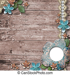 Old wooden background with a frame for photo, flowers, pearls and lace