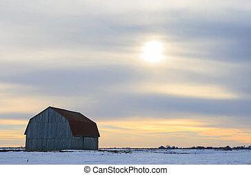 Old wooden barn in a snowy field