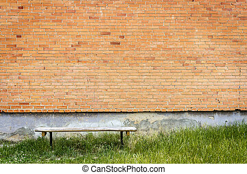 Old wooden bench by red brick wall