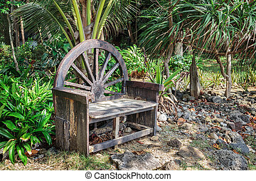 Old wooden bench in a tropical garden