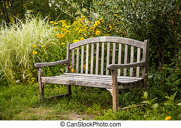 Old Wooden Bench in Garden - An old wooden bench in a public...