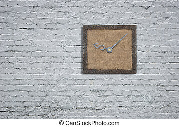 Old wooden board with clock hands on white bricks wall