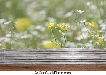 Old wood board with mustard flower field background