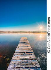 Old Wooden Boards Pier On Calm Lake, River. Autumn Season. Sunse
