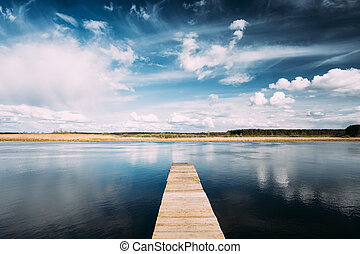 Old Wooden Boards Pier On Calm Water Of Lake Or River At Evening Or Morning Time. Forest On Other Side. Landscape. Nature Background