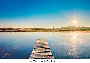 Old wooden boards pier on Calm Water Of Lake, River