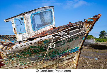 Old wooden boat hull with decayed wood, peeling paint, an abandoned boat in Brittany