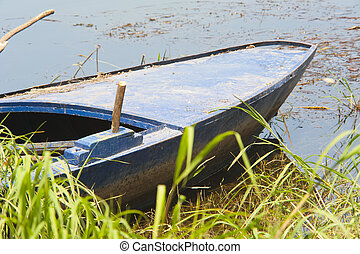 Old wooden boat on a riverbank