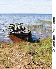 Old wooden boat on lake bank, north Russia