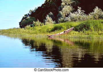 old wooden boat on the river bank close up against the background of green grass and bushes, reflections in the water