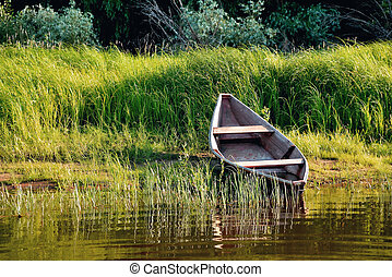old wooden boat on the river bank or clouds close up against the background of green grass and bushes, reflections in the water
