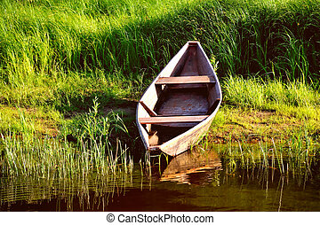 Old wooden boat on the shore, green sedge sunny day toning