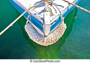 Old wooden boat prow in green water - Old wooden fishing ...