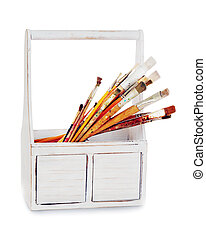 old wooden box with paint brushes isolated on white