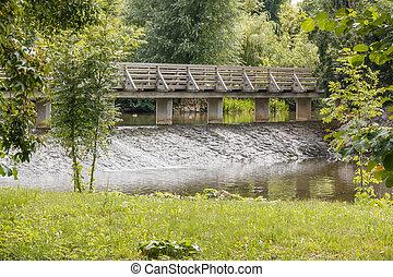 Old wooden bridge above floating river