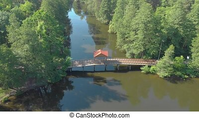 Old wooden bridge aerial over the river in pine forest view push in forward tilt down camera movement