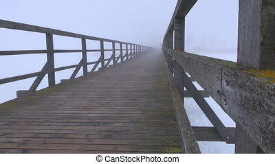 old wooden bridge and mystical fog