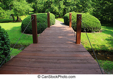 Old wooden bridge in the park in summertime, Cary, North Carolina