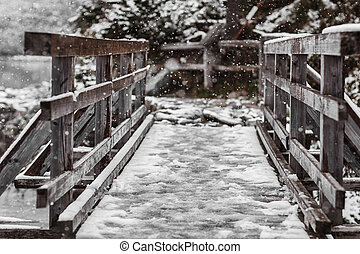 Old wooden bridge in winter in the mountains. Snow-covered bridge over the mountain river