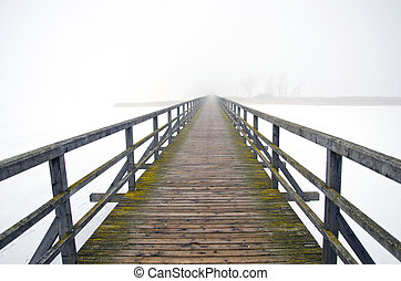 old wooden bridge in winter morning fog
