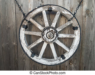 Old wooden cart wheel on a gray wooden wall