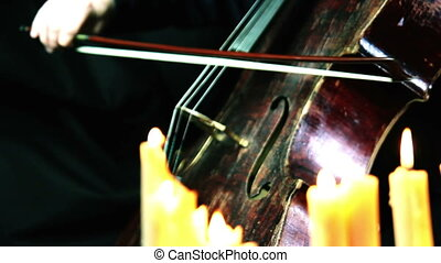 old wooden cello playing in a candles light - camera moving on a dolly