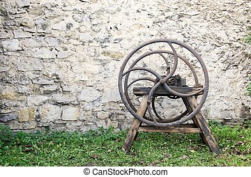 Old wooden chaff cutter standing on grass in front of stone...