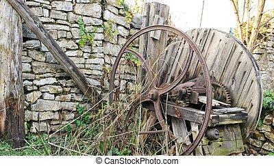 Old wooden chaff cutter standing on grass
