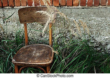 old wooden chair and grass in backyard on background of aged house, calm summer moment, space for text