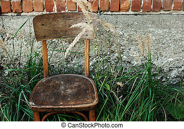 old wooden chair and grass in backyard on background of aged house in village, peaceful calm summer moment