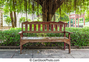 Old wooden reclining chair in a garden.