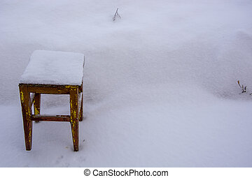 Old wooden chair in the snow. Stool in a snowdrift. There is a lot of snow in the garden in winter.