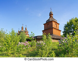 Old wooden church and lilac trees