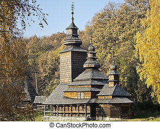 old wooden church in the background of the autumn landscape